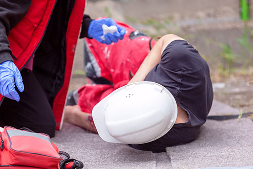 giving emergency first aid to a construction worker